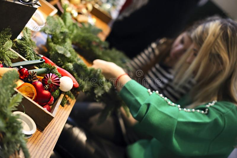 Family making christmas wreath from fir branches, christmas balls and pine cones on the wooden table stock images