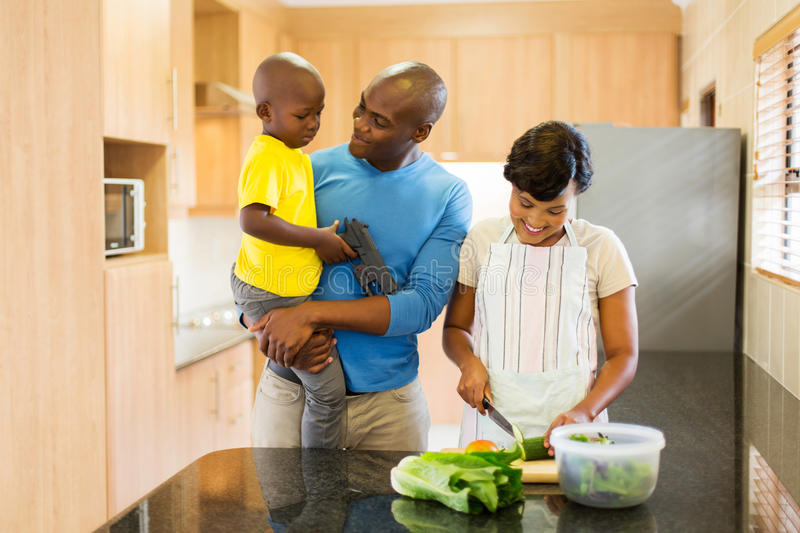 Family making salad. Happy young african american family making salad in kitchen royalty free stock photos