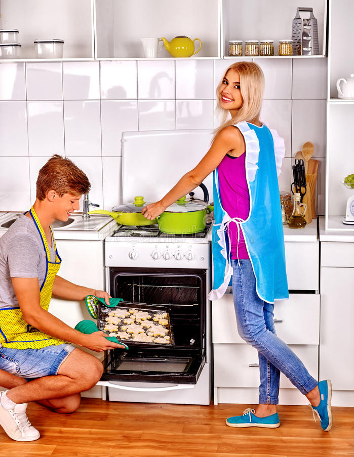 Family man and woman baking cookies in oven. royalty free stock photo