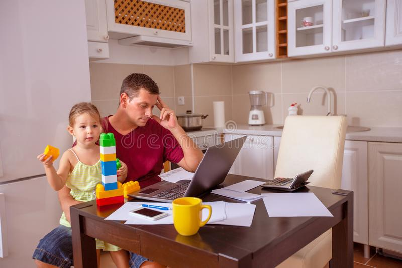 Family - man working with computer while looking after his daughter royalty free stock photos