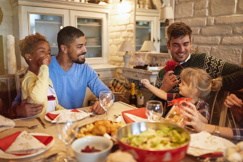 Family x-mas dinner - daddy with daughters enjoy Christmas dinner stock image