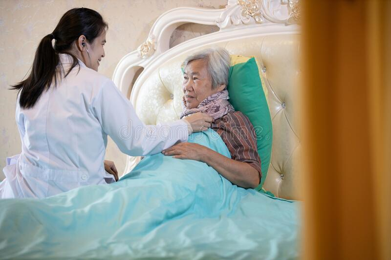 Family medical female doctor or nurse checking heart and lungs of senior patient using stethoscope in bed at home,asian caregiver royalty free stock photos