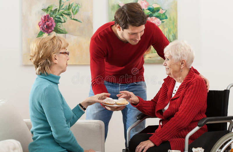 Family meeting. Family keeping company to elder disabled person stock image