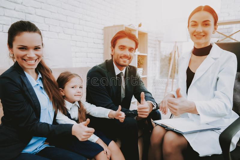 Family Meeting with Professional Psychologist. Happy Family. Psychologist in White Coat. Brown Sofa. Psychologist`s Office. Write Recommendations. Notepad and royalty free stock photography