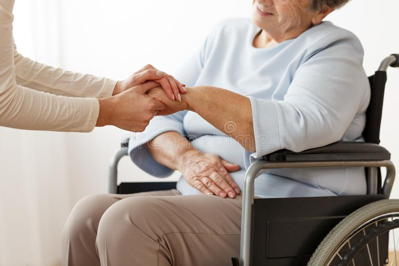 Family member supporting disabled grandmother. Close-up of family member helping disabled grandmother in a wheelchair royalty free stock photo