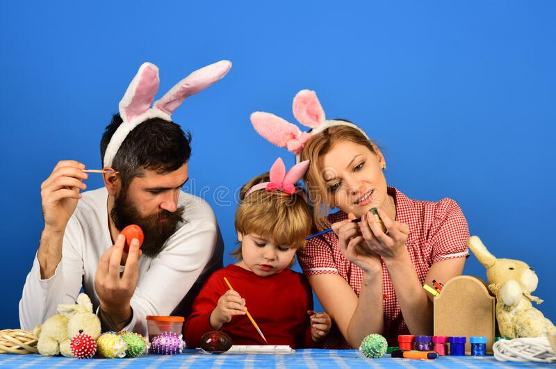 Family members painting eggs on blue background stock photography