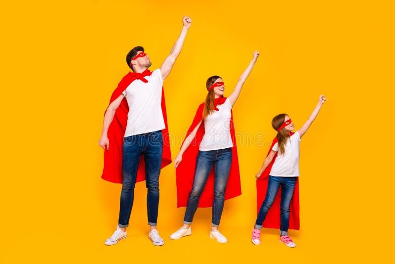 Family members playing cartoon incredible characters saving world wear superhero flying coats isolated yellow background. Family members playing cartoon royalty free stock image