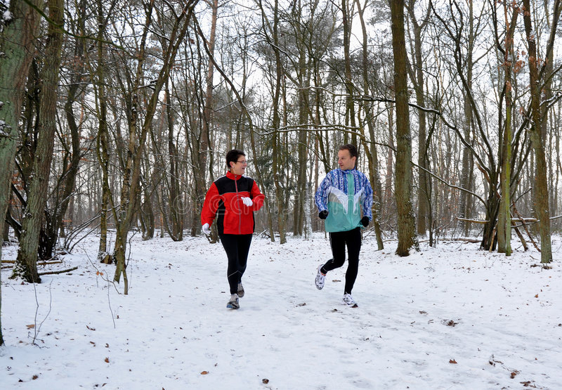 Family members running in the snow. Family members running in the winter royalty free stock photo