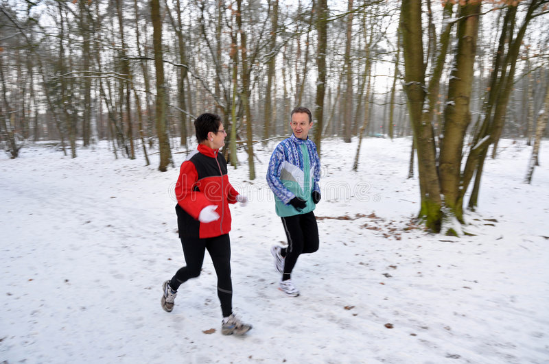Family members running in the snow. Family members running in the winter stock photos