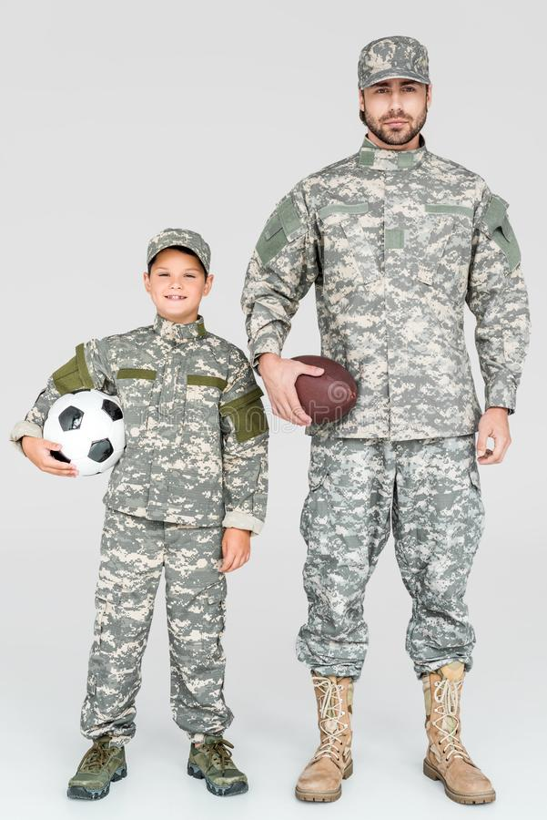 family in military uniforms holding soccer and rugby balls stock photo