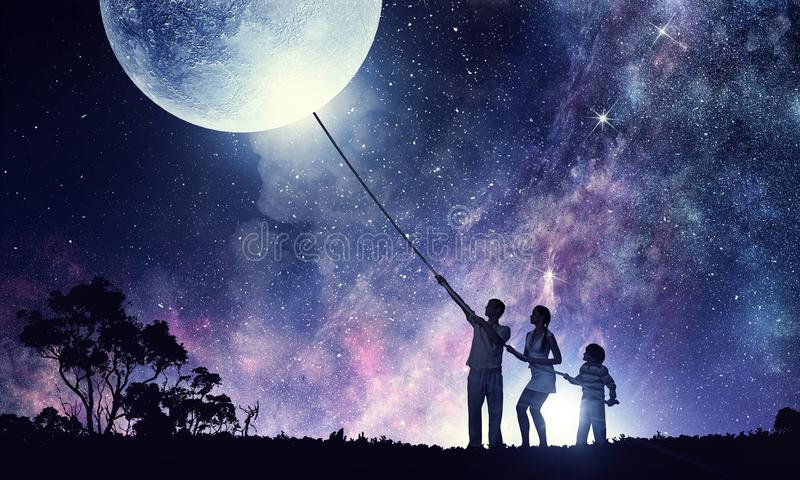 We are family. Mixed media. Silhouette of young happy family pulling moon. Mixed media stock photography