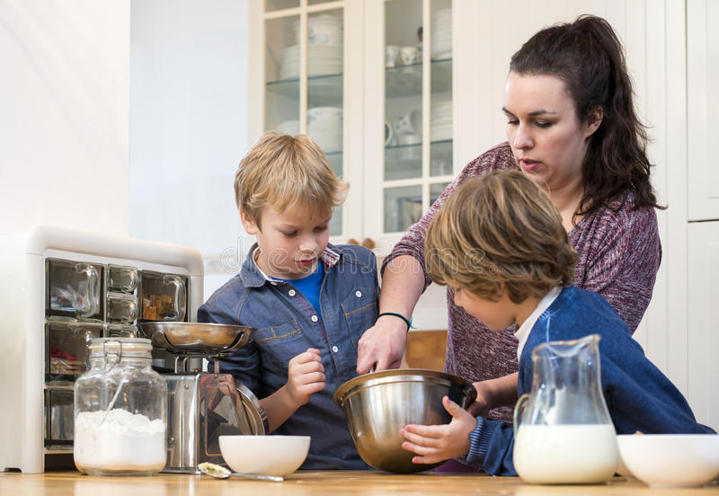 Family Mixing Cupcake Batter In Kitchen stock image