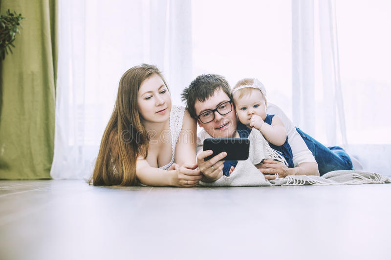 Family mom, dad and baby are doing selfie on phone lying on the stock images