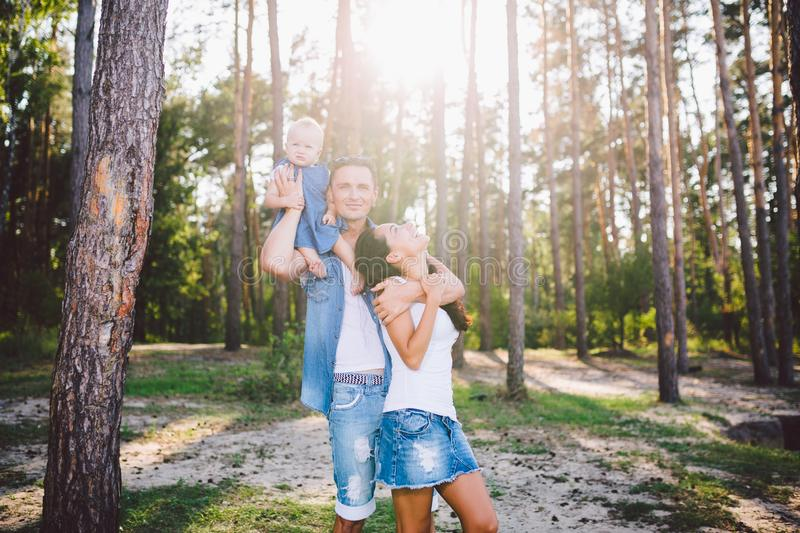 Family mom, dad and daughter sits at the daddy on the shoulders, and parents kiss on the nature in the forest in the summer at. Sunset royalty free stock image