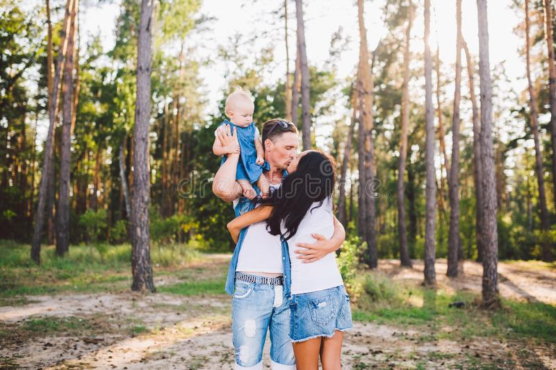 Family mom, dad and daughter sits at the daddy on the shoulders, and parents kiss on the nature in the forest in the summer at. Sunset royalty free stock photography