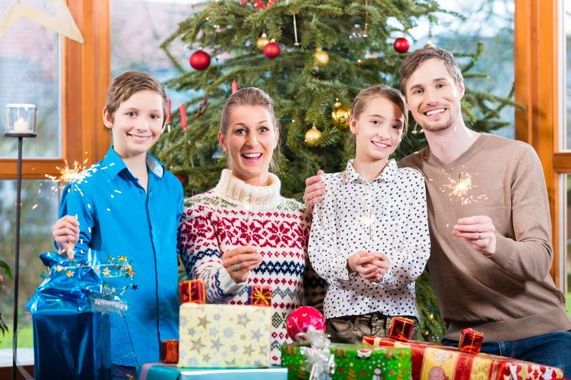 Family of mom, dad and kids with presents under Christmas tree stock images