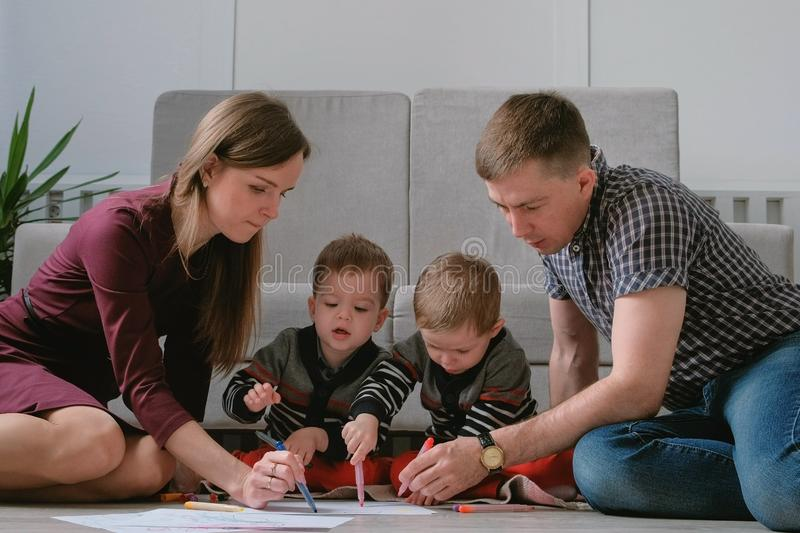 Family mom, dad and two twin brothers draw together markers and felt pens sitting on the floor. royalty free stock photography