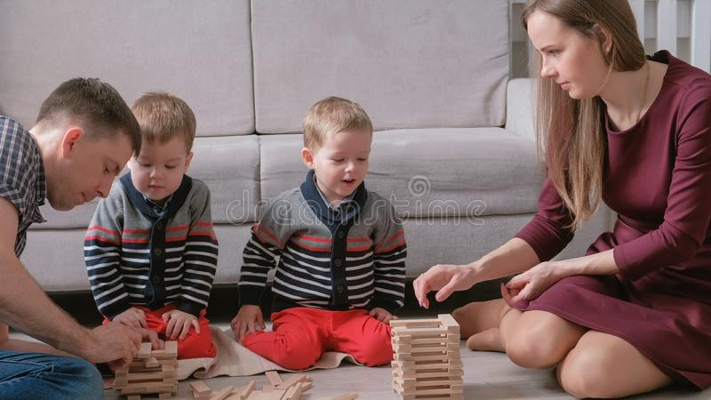 Family mom, dad and two twin brothers play together building out of wooden blocks on the floor. stock image