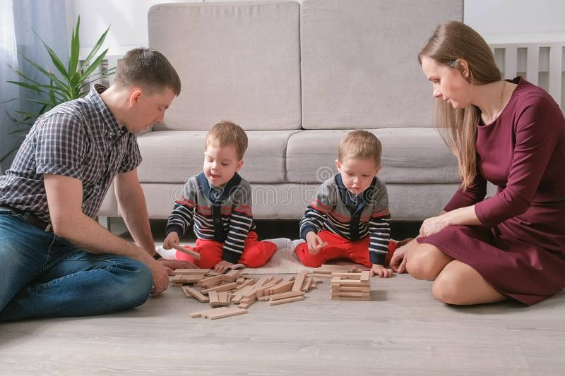 Family mom, dad and two twin brothers play together building out of wooden blocks on the floor. royalty free stock photography