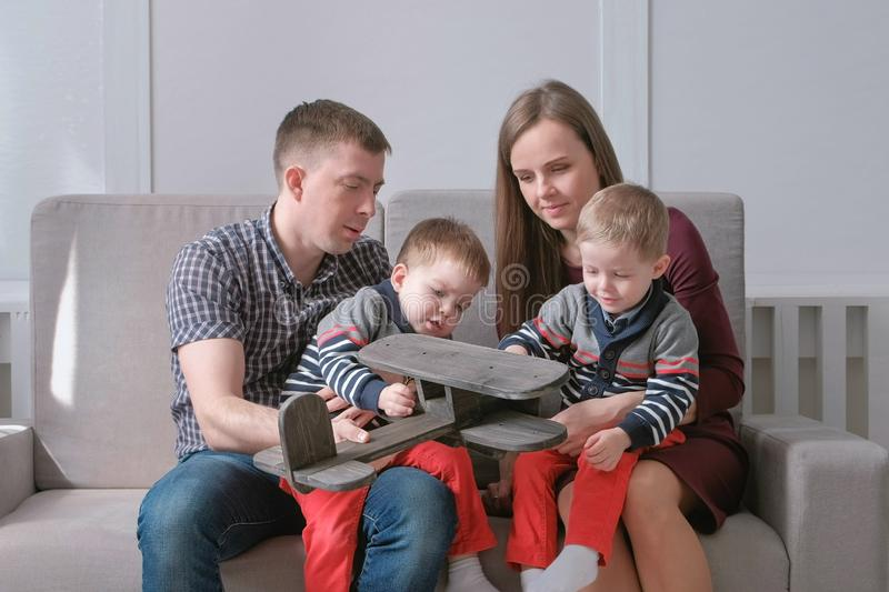 Family mom, dad and two twin brothers read books sitting on the sofa. Family reading time. royalty free stock photography