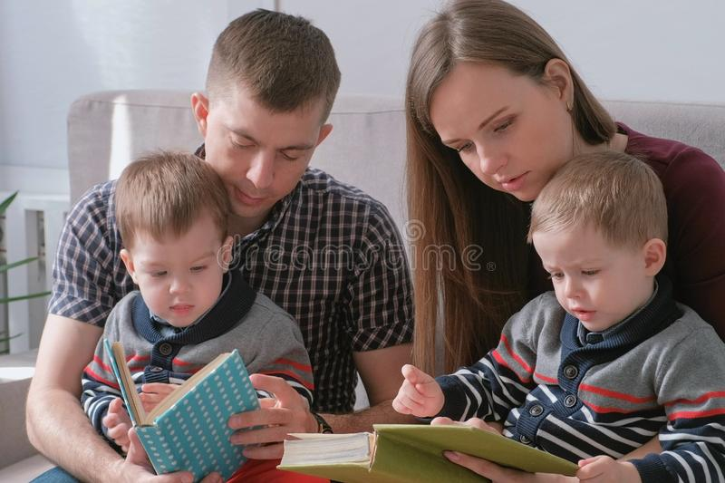 Family mom, dad and two twin brothers read books sitting on the sofa. Family reading time. stock image