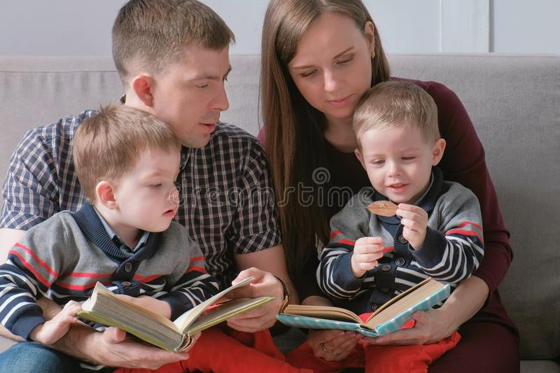 Family mom, dad and two twin brothers read books sitting on the sofa. Family reading time. royalty free stock images