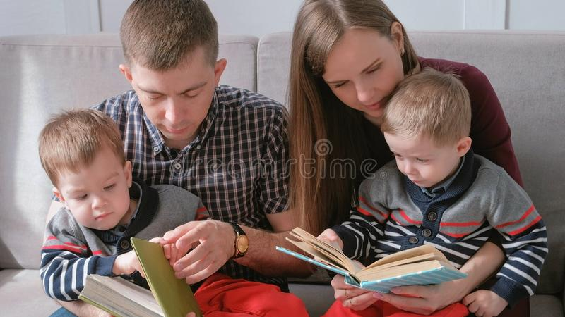 Family mom, dad and two twin brothers read books sitting on the sofa. Family reading time. stock photo