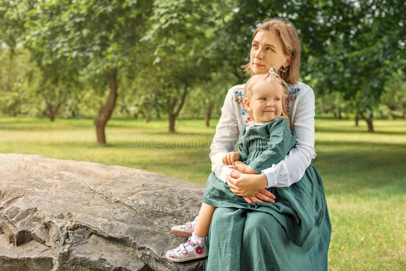 Family mom with daughter in vintage retro linen dresses sitting on a stone rock in the park forest in a thoughtful state and stock photography