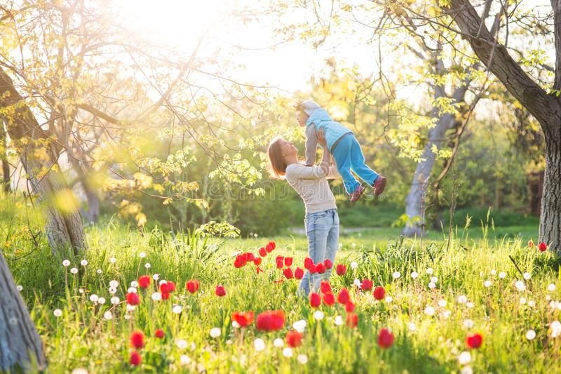 Family mom with daughter woman with child in spring stand and hug on a glade with green grass and tulips royalty free stock images