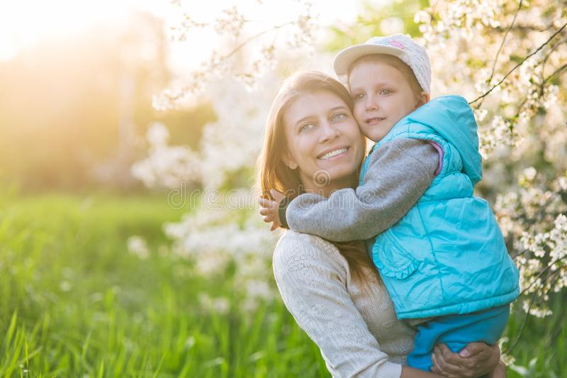 Family mom with daughter woman with child in spring stand and hug royalty free stock photo
