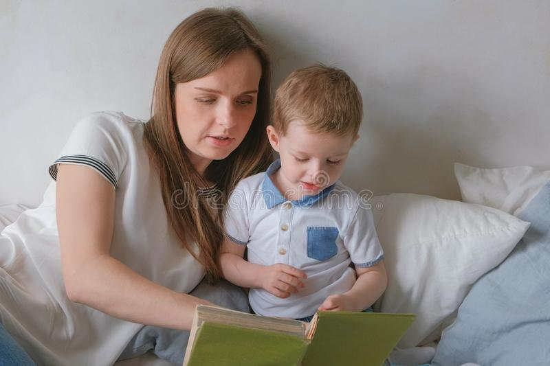 Family mom and son toddler read books laying on the bed. Family reading time. stock photo