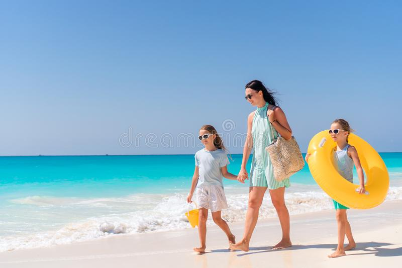 Adorable little girls and young mother on white beach stock image