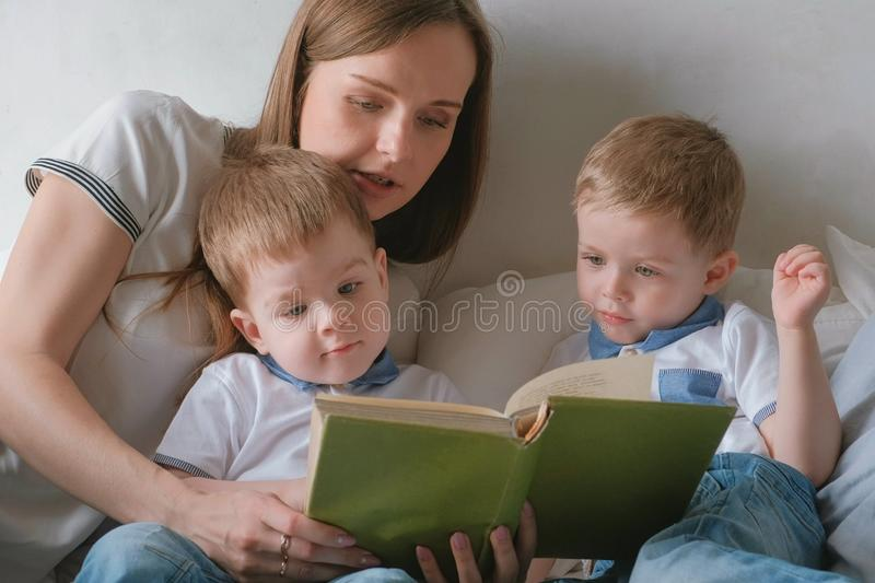 Family mom and two twin brothers toddlers read books laying on the bed. Family reading time. royalty free stock photo