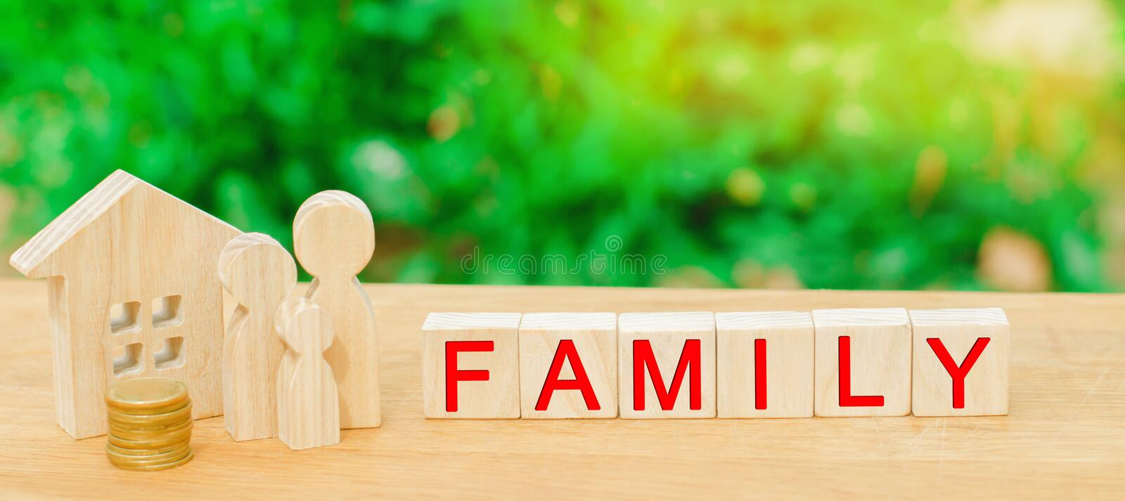The family with money is standing near their house. concept of wealth life and a happy well-endowed. inscription `family` on woode. N blocks. insurance. savings royalty free stock photo