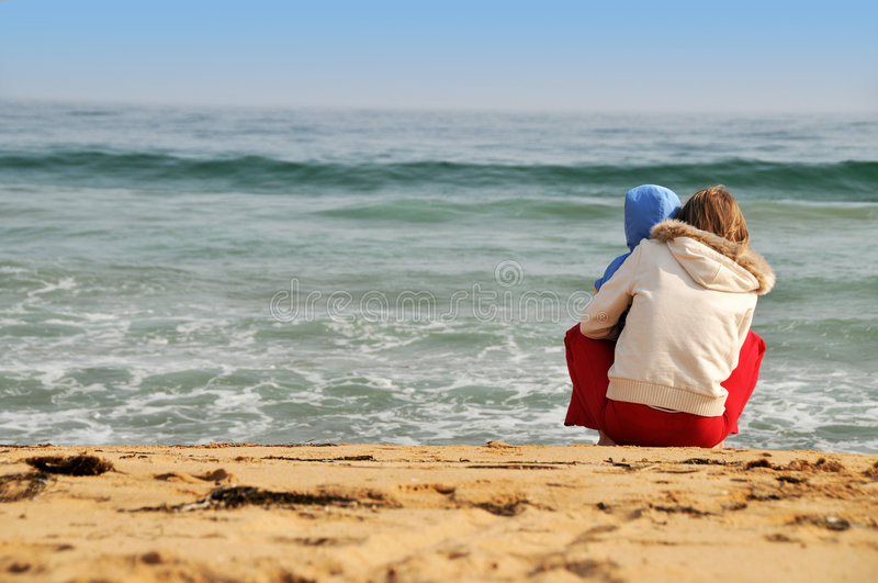 Family of mother with baby on the sea beach royalty free stock photo