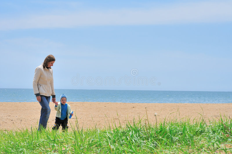 Family of mother and baby walking on the sea beach royalty free stock photos