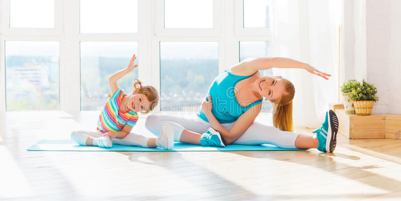 Family mother and child daughter are engaged in fitness, yoga at royalty free stock photos