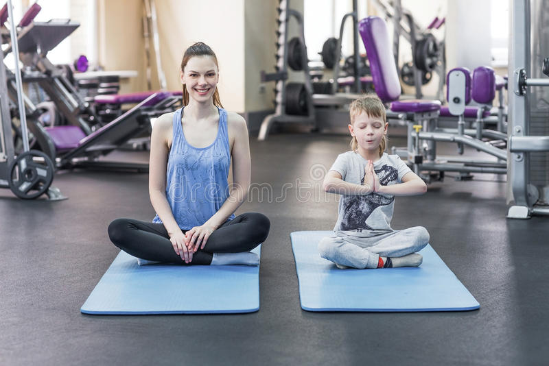 Family mother and child daughter are engaged in meditation and yoga royalty free stock photo
