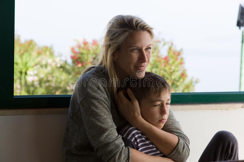 Blonde mother smiles and holds her young child between her arms royalty free stock images