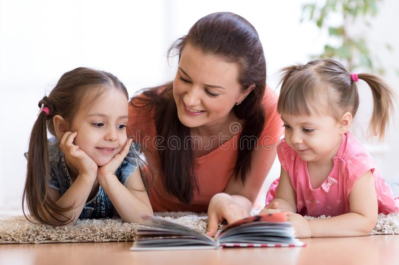 Cute mother and children daughters lie on floor and read book together. Family - mother and children daughters lie on floor and read book together royalty free stock photography