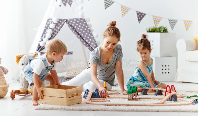 Family mother and children play a toy railway in playroom. Family mother and children play a toy railway in the playroom stock photos