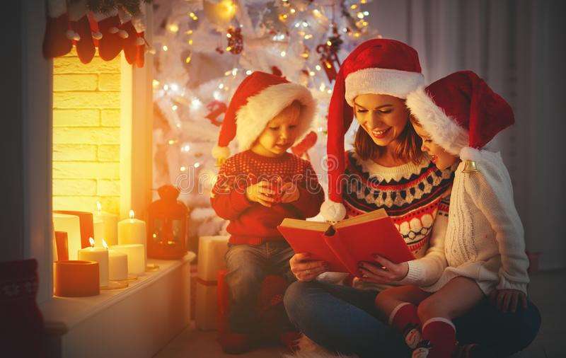Family mother and children read a book at christmas near firep. Happy family mother and children read a book at christmas near fireplace at home stock photo