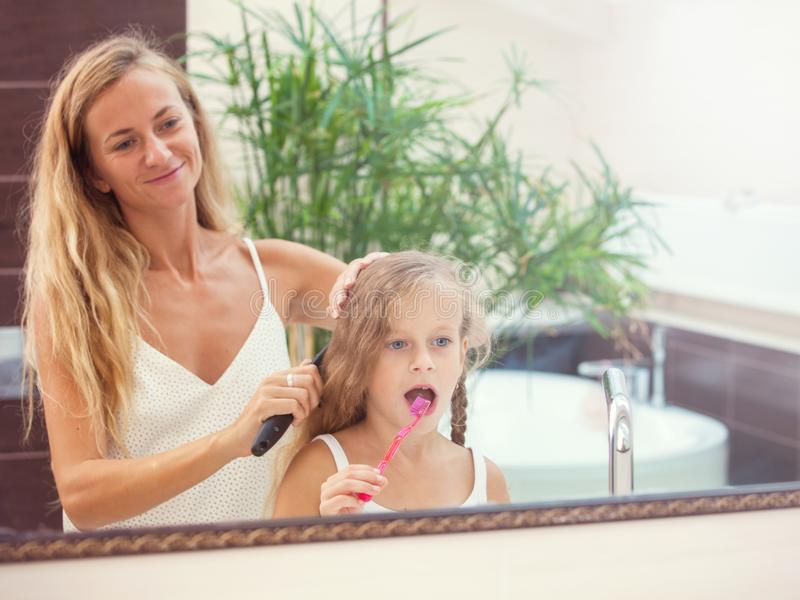 Family. Mother and daughter brushing their teeth royalty free stock photos
