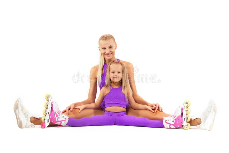 Family, mother and daughter, posing in studio wearing inline rollerskates stock image