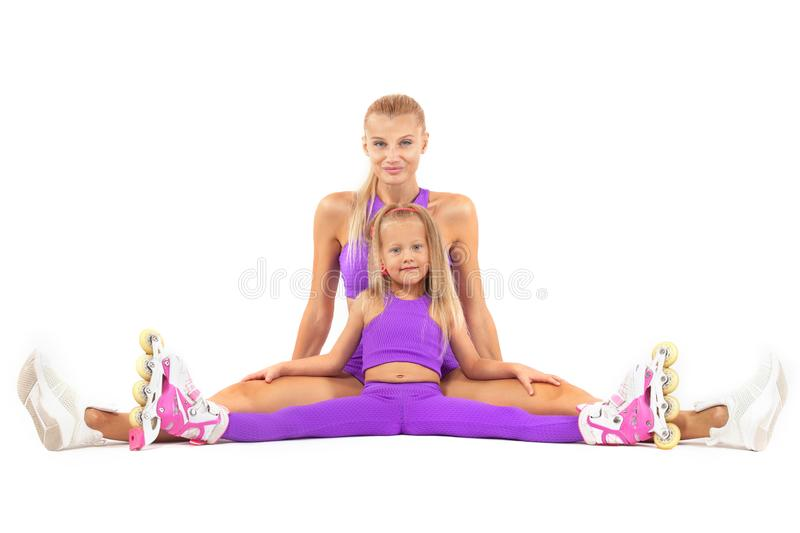 Family, mother and daughter, posing in studio wearing inline rollerskates. Good looking family, mother and daughter, posing in studio wearing inline roller royalty free stock photos