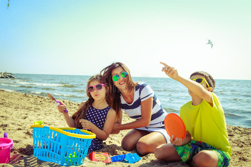 Family mother daughter son having fun on beach. royalty free stock image