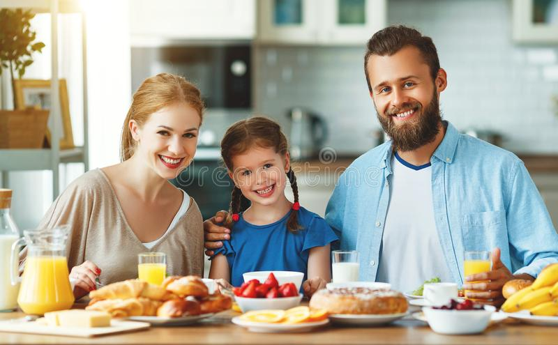 Family mother father and child daughter have Breakfast in kitchen in morning royalty free stock photography