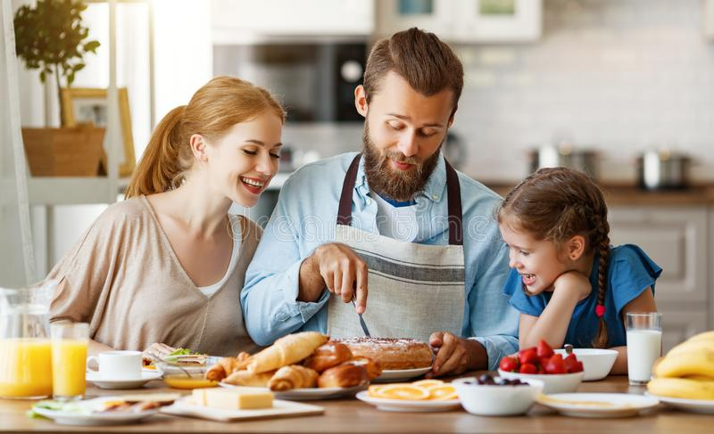 Family mother father and child daughter have Breakfast in kitchen in morning. Family mother father and child daughter have Breakfast in the kitchen in morning stock photos
