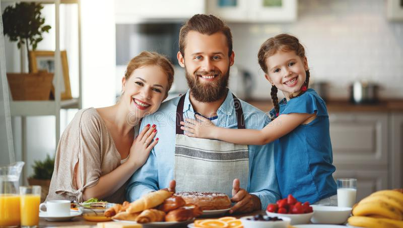 Family mother father and child daughter have Breakfast in kitchen in morning stock images