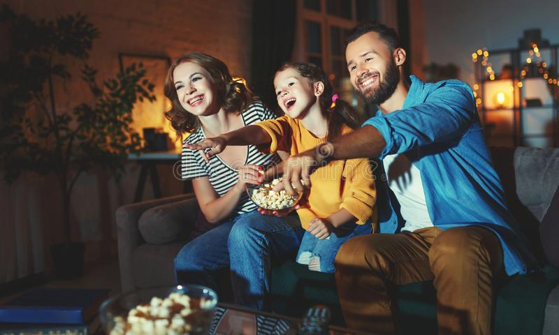 Family mother father and child daughter watching projector, TV, movies with popcorn in   evening   at home stock images